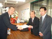 要請署名を渡す新山税金対策部長(中)