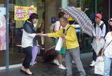 悪天候の中、チラシを配布する横山委員長