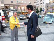 チラシを渡す新山税対部長(左)