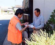 熱心に組合の説明をし、組合パンフレットを手渡す組合役員(左)