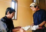 現場を訪問し、職人さんにパンフレットを渡す役員(左)