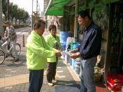 金物店にて店主に組合パンフレットを店頭に置いていただくように依頼する役員(左・中央)