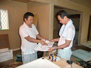 建設現場で未加入者の方に組合制度を説明する宮上支部長(左)