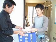 建設現場へ訪問し、組合未加入者の職人さんへ組合パンフレットを手渡す役員(左)