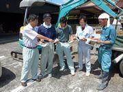 建築現場で職人さんに組合の説明をする植田支部長(左)
