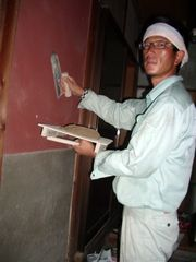壁塗り作業をする佐野副部長