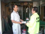 役員から熱心な組合説明を受け、組合パンフレットを受取るガラス店のご主人(左)