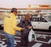 買い物を終えた職人さんに声掛けする役員(左)