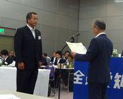 組織拡大功労者表彰を受ける野田支部長(左)