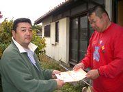 組合の資料を手渡す役員(左)