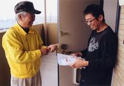 組合員さん宅へ訪問し、組合説明をする横山支部長(左)