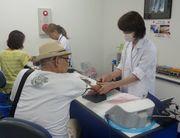 組合が実施する集団健康診断を受ける組合員(左)