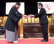 市長から表彰を受ける堀さん(右)